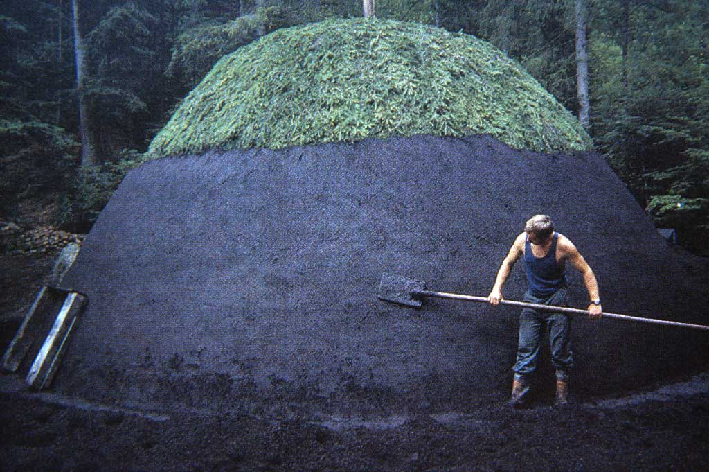 A charcoal producer applying the Löschi (granulated carbon) to insulate the pile. At the top the covering of Reisig (branches of fir trees) is visible, between 1980 and 2005 © Paul Duss, Romoos