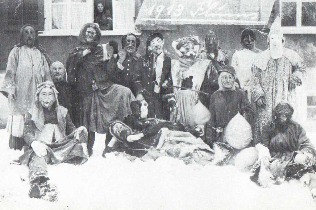 Flums street carnival with a group of masked participants in used 'Huttlen', 1913