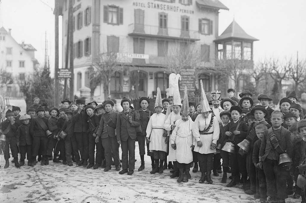 Schoolboys with cowbells on a Santa Claus procession in Stans. At the centre are the Geiggel (wearers of decorative headpieces typical of the area). Around 1900 © Staatsarchiv Nidwalden