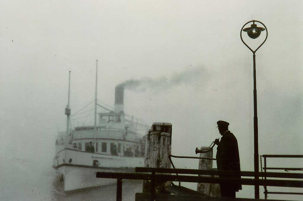 Station attendant on the landing bridge with a foghorn, around 1920. © Schifffahrtsgesellschaft des Vierwaldstättersees